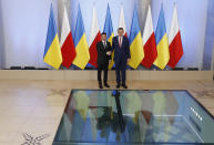 Poland's Prime Minister Mateusz Morawiecki, right, welcomes Ukraine's President Volodymyr Zelenskiy as they meet in Warsaw, Poland, Saturday, Aug. 31, 2019. Zelenskiy is in Warsaw with members of his new Cabinet and will attend ceremonies marking 80 years of the start of World War II on Sunday. (AP Photo/Petr David Josek)