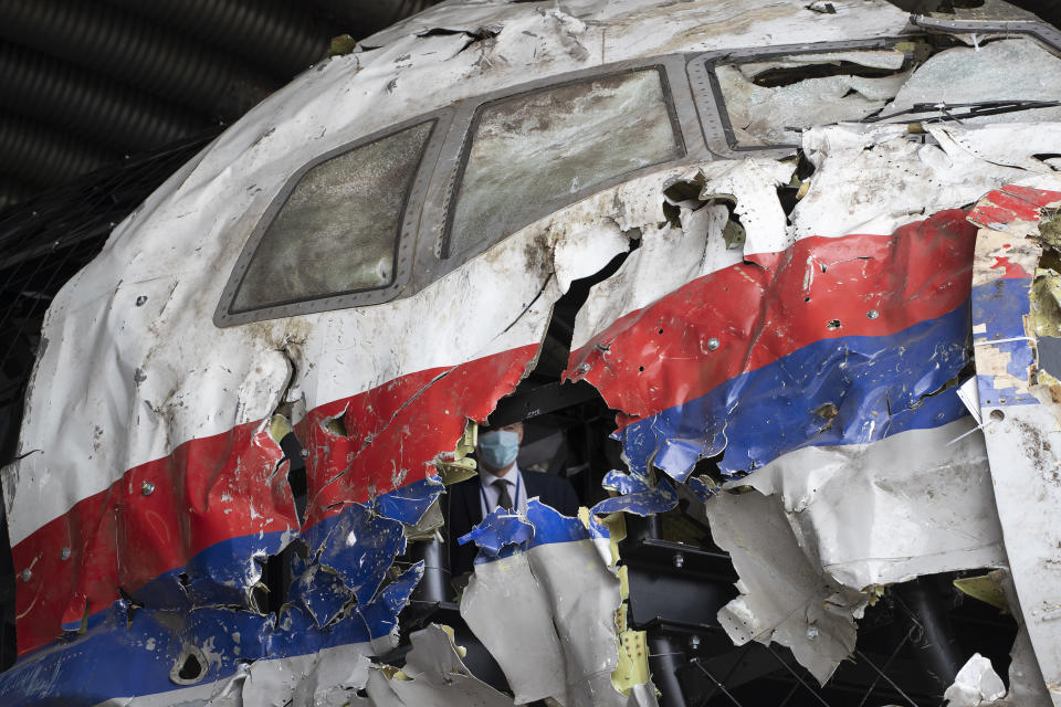 FILE- In this Wednesday, May 26, 2021, file photo presiding judge Hendrik Steenhuis is seen inside the cockpit as he and other trial judges and lawyers view the reconstructed wreckage of Malaysia Airlines Flight MH17, at the Gilze-Rijen military airbase, southern Netherlands. The trial in absentia in a Dutch courtroom of three Russians and a Ukrainian charged in the downing of Malaysia Airlines flight MH17 in 2014 moves to the merits phase, when judges and lawyers begin assessing evidence. (AP Photo/Peter Dejong, File)