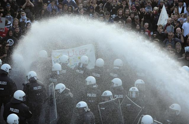 <p>Police and demonstrators are sprayed by a water cannon during a protest against the G-20 summit in Hamburg, northern Germany, Thursday, July 6, 2017. (Photo: Markus Schreiber/AP) </p>