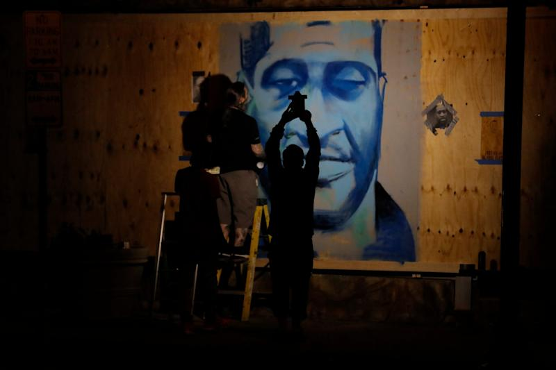 An artist creates an image of George Floyd in Minneapolis as protests over his death broke out in Minneapolis for a third straight night: AP