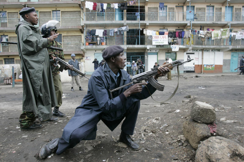 FILE - In this Jan. 20, 2008 file photo, Kenyan police officers react as opposition supporters throw stones at them during post-election violence in the Mathare slum of Nairobi, Kenya. The families of seven people shot dead five years ago and eight wounded survivors this week filed a lawsuit to sue the Kenyan government over police brutality in the violence that followed the country's 2007 election, which comes as Kenya prepares for a new election on March 4, 2013 amid warnings from international human rights groups that the police are not ready to prevent electoral violence while refraining from human rights violations. (AP Photo/Karel Prinsloo, File)