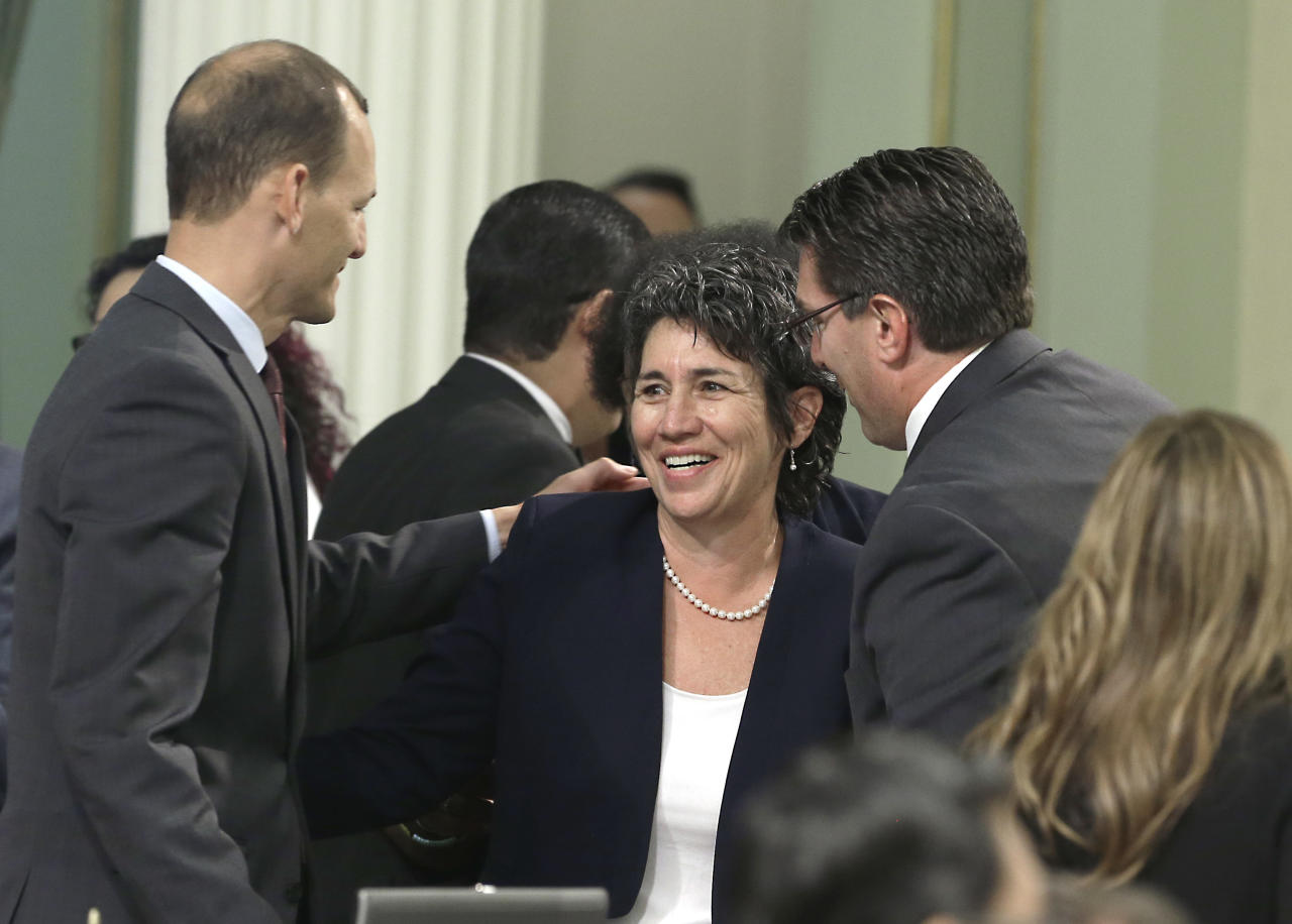 FILE - In this Sept. 9, 2015, file photo, assemblywoman Susan Talamantes Eggman, D-Stockton, is congratulated by assembly members Kevin McCarty, D-Sacramento, left, and Jay Obernolte, R-Big Bear Lake, after her right-to die measure was approved by the state Assembly in Sacramento, Calif. California health officials reported Tuesday, June 27, 2017, that 111 terminally ill people took drugs to end their lives in the first six months after a 2016 law made the option legal in the nation's most populous state. (AP Photo/Rich Pedroncelli, File)
