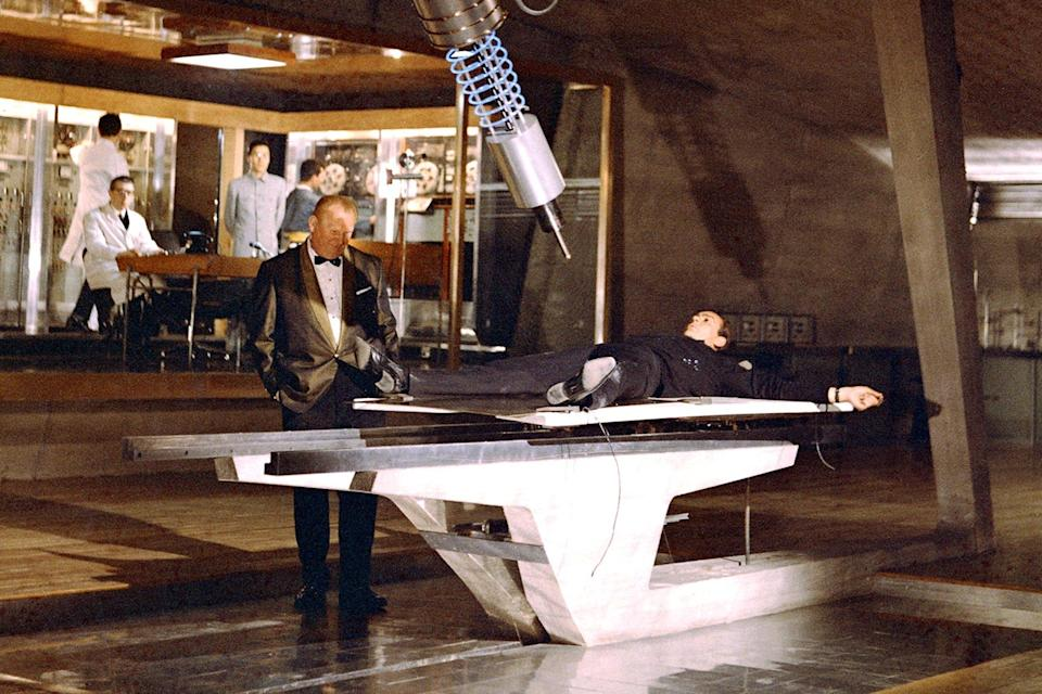 """<p>As a rule of thumb, each 007 installment builds to at least one fateful showdown when it seems as if Bond has finally reached the end of his road, where even a well-timed wisecrack won't save him. Still, none is more memorable than the torture scene between Auric Goldfinger and Connery's 007, when our hero is strapped to a table in the Midas-minded villain's lair with a laser aimed at his crown jewels. """"Choose your next witticism carefully, Mr. Bond, it may be your last."""" As the laser starts inching ever-so precariously northward, the squirming 007 asks, """"Do you expect me to talk?"""" To which Goldfinger offers the wonderfully evil one-liner: """"No, Mr. Bond, I expect you to die!""""</p>"""