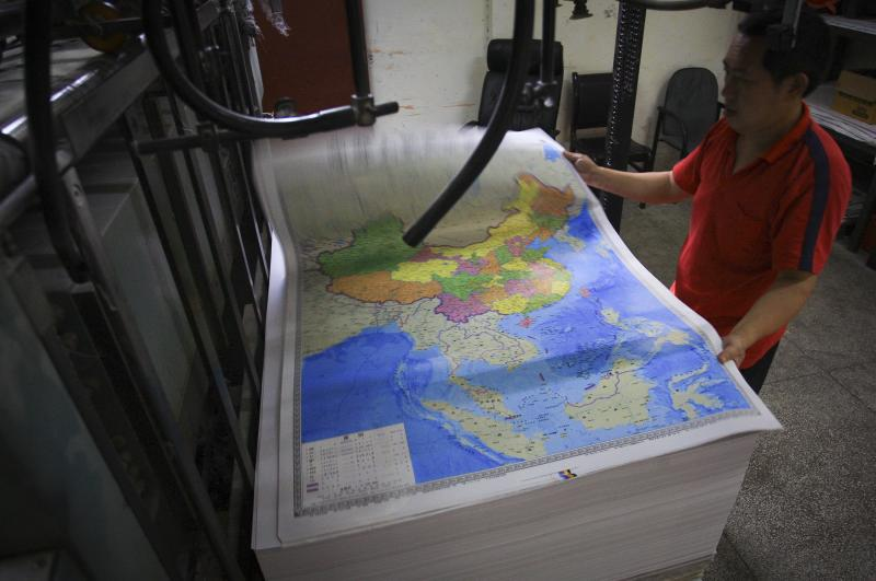 A worker checks on a new official map of China at a printing house in Changsha