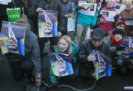 """Protesters hold upturned portraits of Ukrainian President Viktor Yanukovich and journalist Tetyana Chornovil, who was beaten and left in a ditch just hours after publishing an article on the assets of top government officials, during a protest rally in front of the Ukrainian Ministry of Internal Affairs in Kiev, December 26, 2013. The text on the portraits reads """"Upturn"""" (which in Ukrainian is synonymous with coup). REUTERS/Gleb Garanich"""