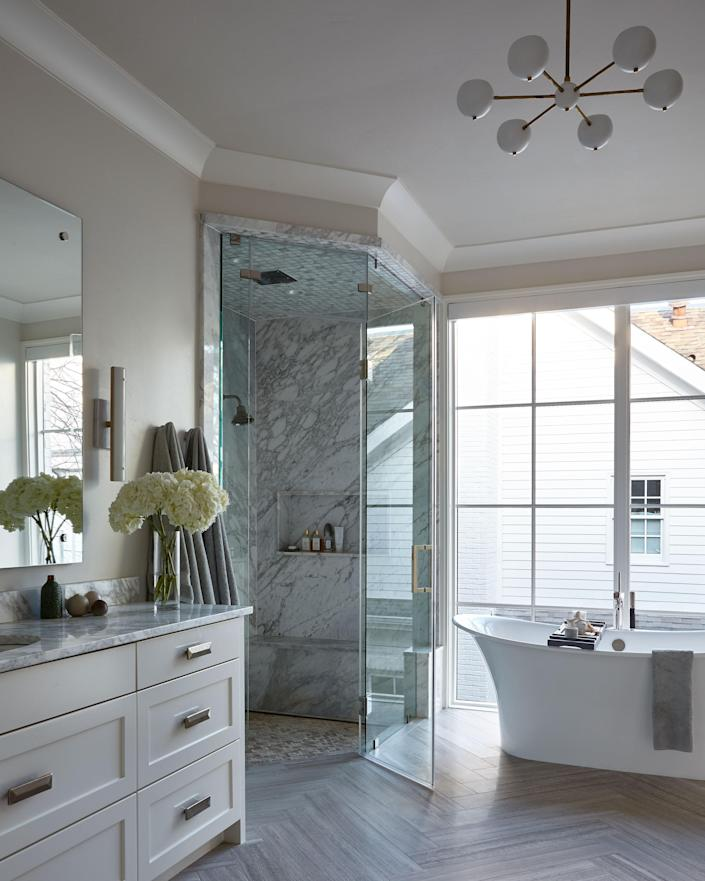 """The main bath features a ceiling light from Blueprint Lighting and LED sconces from <a href=""""https://www.rollandhill.com/products/counterweight-sconce"""" rel=""""nofollow noopener"""" target=""""_blank"""" data-ylk=""""slk:Roll & Hill"""" class=""""link rapid-noclick-resp"""">Roll & Hill</a>."""