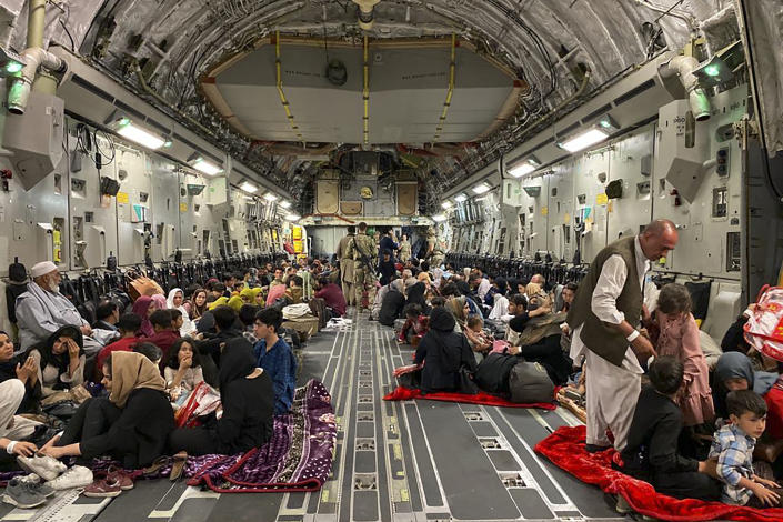 TOPSHOT - Afghan people sit inside a U S military aircraft to leave Afghanistan, at the military airport in Kabul on August 19, 2021 after Taliban's military takeover of Afghanistan. (Photo by Shakib RAHMANI / AFP) (Photo by SHAKIB RAHMANI/AFP via Getty Images)