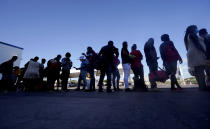 Migrants, mostly from Haiti, wait for a bus after they were processed and released after spending time at a makeshift camp near the International Bridge, Sunday, Sept. 19, 2021, in Del Rio, Texas. President Joe Biden's administration is nearing a final plan to expel many of the thousands of Haitian migrants who have suddenly crossed into a Texas border city from Mexico and to fly them back to their Caribbean homeland. (AP Photo/Eric Gay)