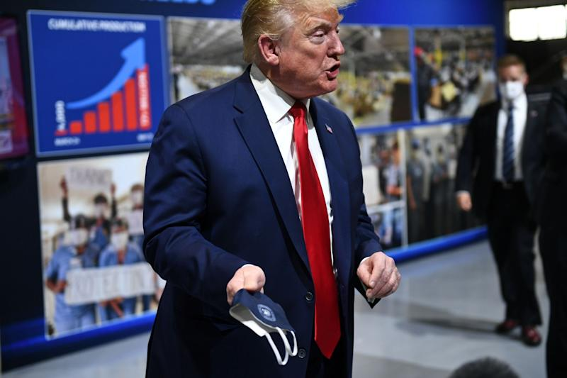 Donald Trump holds a face mask emblazoned with the presidential seal on a visit to a Ford manufacturing plant in Michigan: AFP via Getty Images