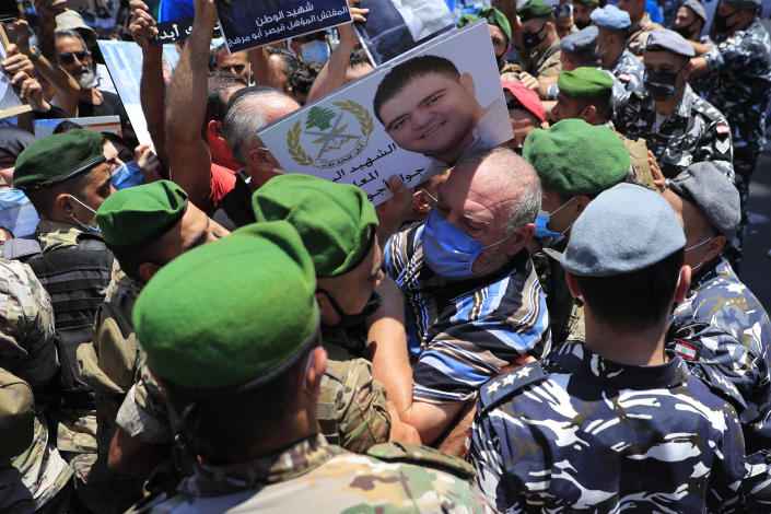 A father of a Lebanese army soldier who killed during the last year's massive blast at Beirut's seaport, holds his son's portrait as he pushed back by Lebanese army soldiers as he trying to reach the tightly-secured residents of parliament speaker Nabih Berri, in Beirut, Lebanon, Friday, July 9, 2021. The protest came after last week's decision by the judge to pursue senior politicians and former and current security chiefs in the case, and requested permission for their prosecution. (AP Photo/Hussein Malla)