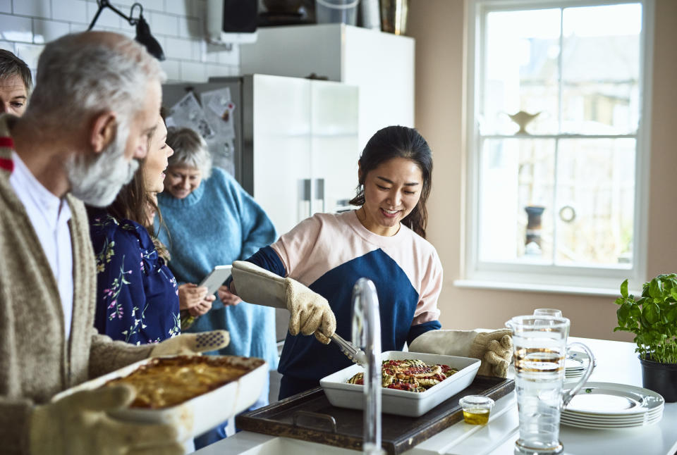 Extended family preparing a meal together, multi racial relatives and different generations, working together as a team and enjoying spending quality time at home
