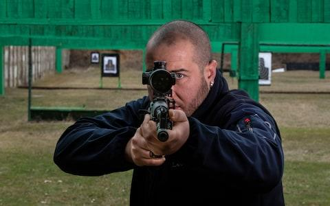 Dimitar Lutzkanov, instructor at the Kazanlak shooting range with an AK47 style assault rifle - Credit: Simon Townsley
