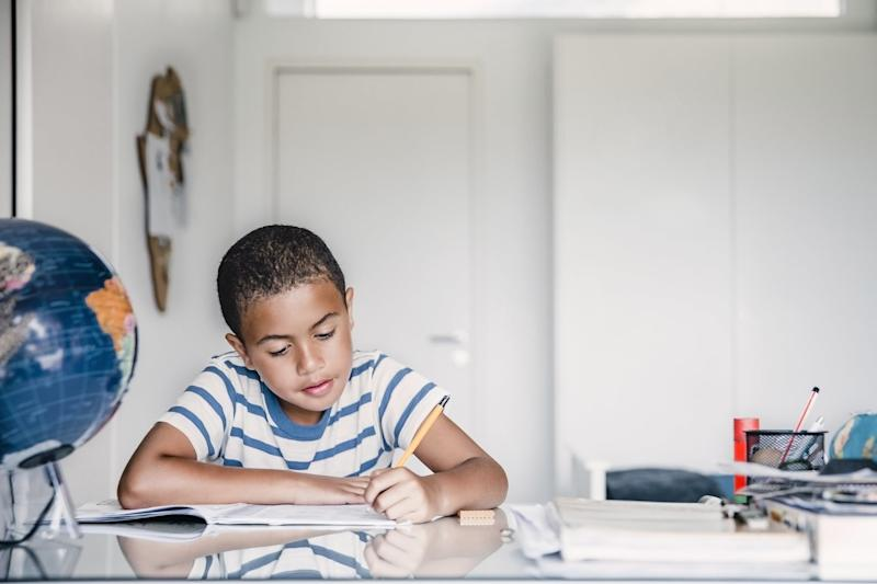 Cute boy studying at table in house