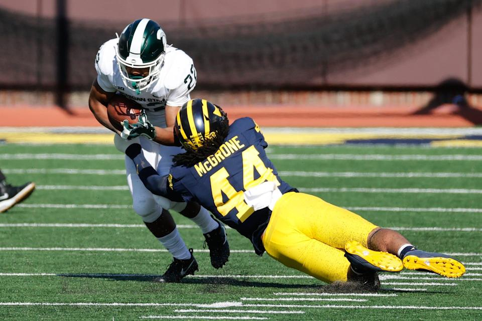 Michigan State running back Jordon Simmons is tackled by Michigan linebacker Cameron McGrone during the first half on Saturday, Oct. 31, 2020, at Michigan Stadium.