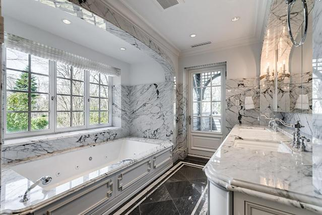<p>The home has five bedrooms, five bathrooms and two half bathrooms. The master ensuite is resplendent in marble with a large soaker tub and double sinks, plus access to a private deck. (Listing via <span>Sotheby's</span>) </p>