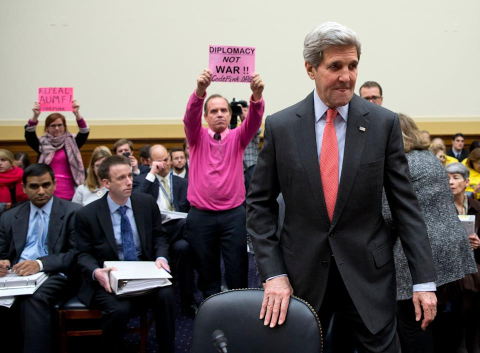 Code Pink protesters hold up a sign as Secretary of State John Kerry arrives on Capitol Hill in Washington on Feb. 25, 2015, to testify before a House Foreign Affairs Committee hearing.