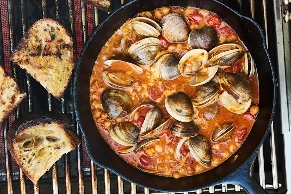 """Don't waste time indoors! Throw a cast-iron pan right on the grill to make this saucy clam and chickpea dish. <a href=""""https://www.epicurious.com/recipes/food/views/chile-lime-clams-with-tomatoes-and-grilled-bread?mbid=synd_yahoo_rss"""" rel=""""nofollow noopener"""" target=""""_blank"""" data-ylk=""""slk:See recipe."""" class=""""link rapid-noclick-resp"""">See recipe.</a>"""