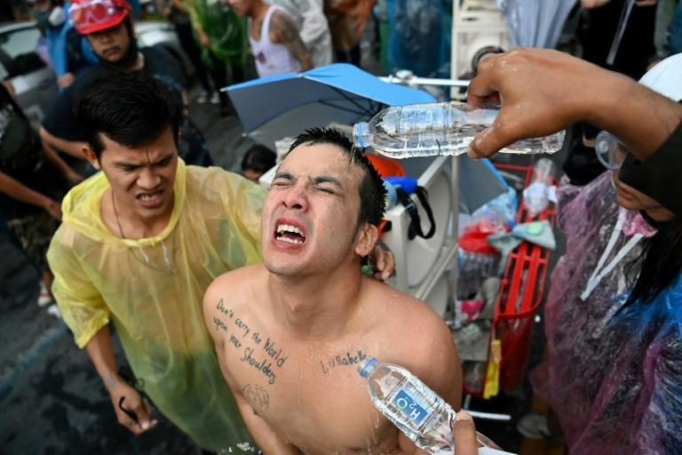 A protester has water poured over his eyes after tear gas was fired during violent clashes in the Thai capital