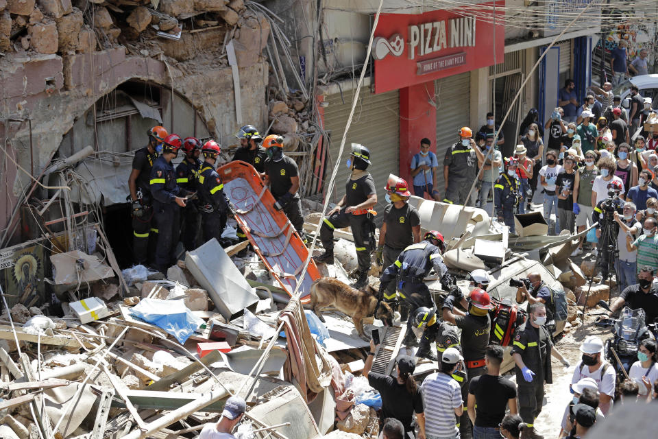 """French and Lebanese firemen search in the rubble of a building after the Tuesday explosion at the seaport of Beirut, in Beirut, Lebanon, Thursday, Aug. 6, 2020. Lebanese officials targeted in the investigation of the massive blast that tore through Beirut sought to shift blame for the presence of explosives at the city's port, and the visiting French president warned that without serious reforms the country would """"continue to sink."""" (AP Photo/Hassan Ammar)"""