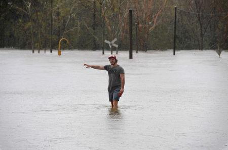 A local resident wades into flood waters blocking the road between the townships of Airlie Beach and Proserpine after Cyclone Debbie hit the area in northern Queensland, located south of Townsville. AAP/Dan Peled/via REUTERS