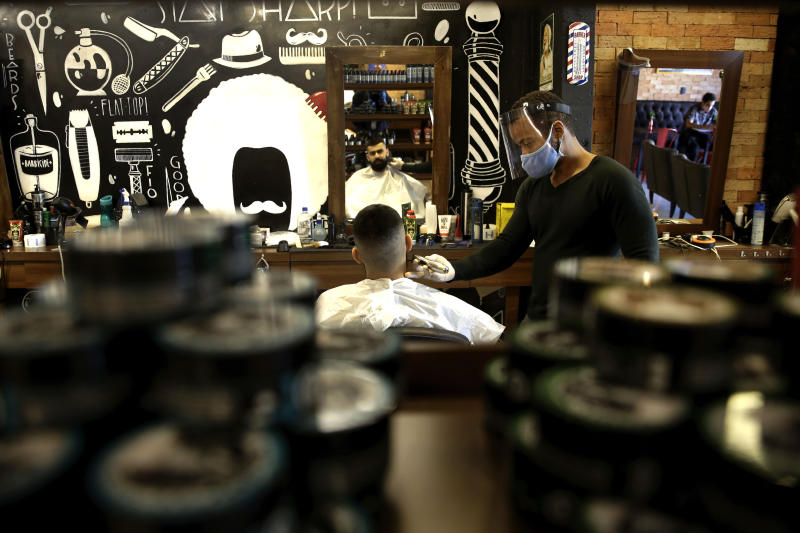 A barber wears a face shield, mask and gloves for protection amid the COVID-19 pandemic while attending a client on the first day the shop was allowed to reopen, as restrictions ease in Brasilia, Brazil, Wednesday, July 15, 2020. (AP Photo/Eraldo Peres)