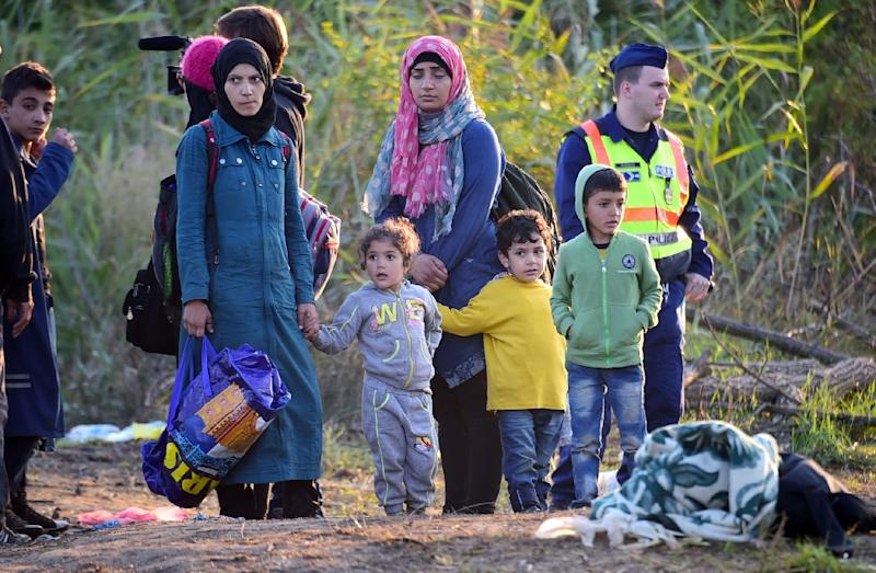 A group of migrant women and children escorted by police wait at a collector point near Roszke village at the Hungarian-Serbian border on August 28, 2015 (AFP Photo/Attila Kisbenedek)