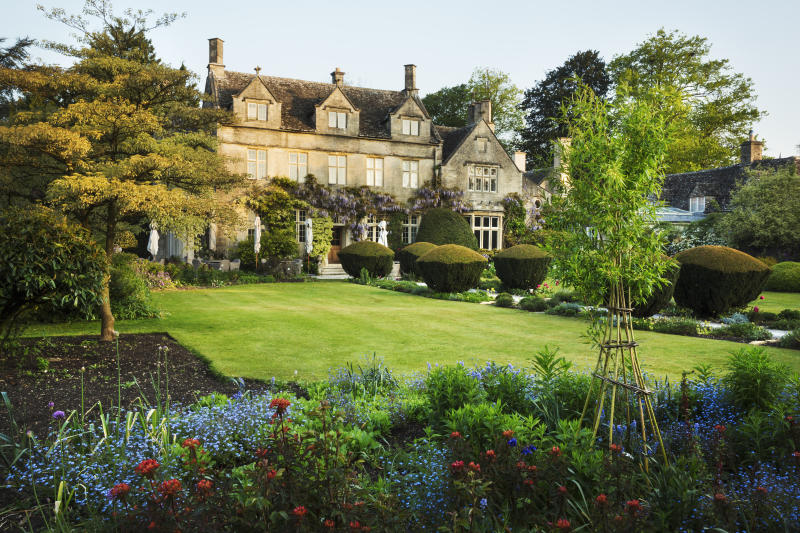 Exterior view of a 17th century country house from a garden with flower beds, shrubs and trees. Photo: Getty