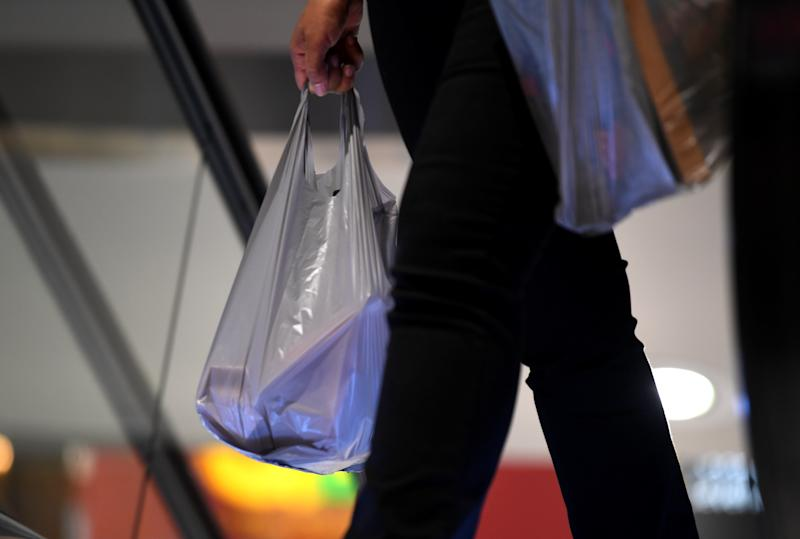 A customer holds a single use plastic supermarket shopping bag.