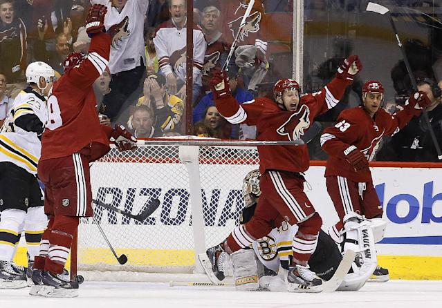 Phoenix Coyotes' Shane Doan, second from left, celebrates his goal against Boston Bruins' Tuukka Rask, bottom right, of Finland, as Coyotes' Brandon McMillan, third from left, and Mike Ribeiro (63) join the celebration as Bruins' Chris Kelly (23) looks on during the first period of an NHL hockey game on Saturday, March 22, 2014, in Glendale, Ariz. (AP Photo/Ross D. Franklin)