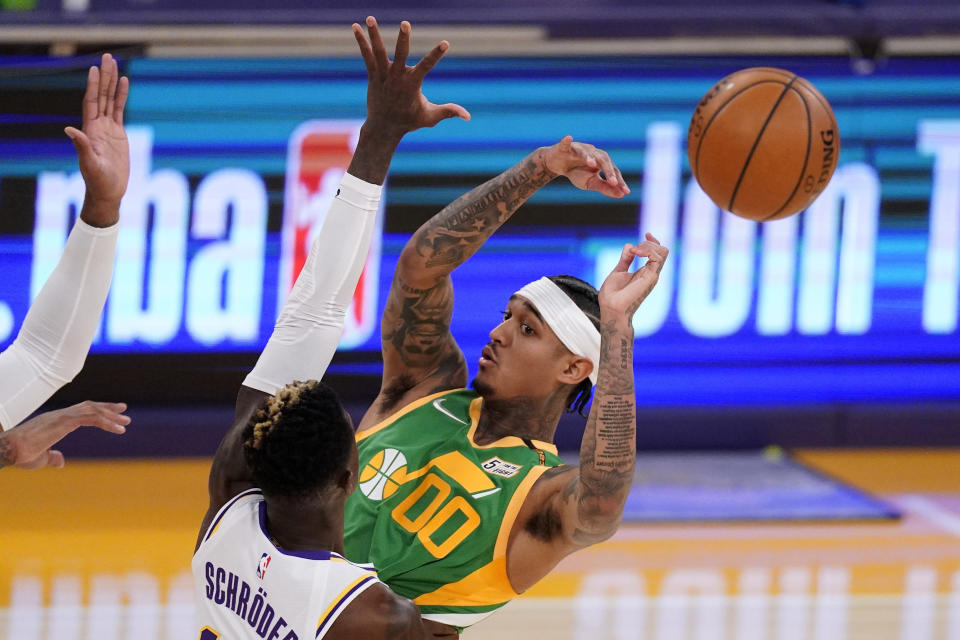 Utah Jazz guard Jordan Clarkson, right, passes the ball as Los Angeles Lakers guard Dennis Schroder defends during the first half of an NBA basketball game Saturday, April 17, 2021, in Los Angeles. (AP Photo/Mark J. Terrill)