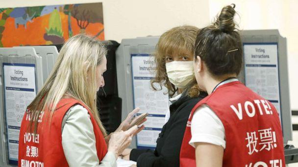 PHOTO: Poll workers speak to a woman wearing a face mask in a polling site at San Francisco City Hall on Super Tuesday, March 3, 2020, in San Francisco. (John G. Mabanglo/EPA via Shutterstock)