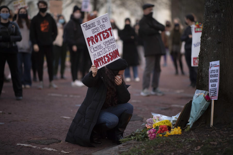 CARDIFF, WALES - MARCH 17: A woman holds her hand to her face after laying flowers at the base of a tree during a protest outside Cardiff Central Police Station on March 17, 2021 in Cardiff, Wales. Legislation giving police greater power to crack down on protests has passed its second reading in the House of Commons with a majority of 96 votes, amid anger at the way officers broke up a vigil for Sarah Everard where women were handcuffed and arrested. Sarah Everard, 33, disappeared after walking home from a friend's house on March 3. Wayne Couzens, 48, has been charged with the 33-year-old's kidnap and murder. (Photo by Matthew Horwood/Getty Images)