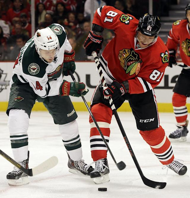 Minnesota Wild's Justin Fontaine (14) and Chicago Blackhawks' Marian Hossa (81) battle for the puck during the first period of an NHL hockey game in Chicago, Saturday, Oct. 26, 2013. (AP Photo/Nam Y. Huh)