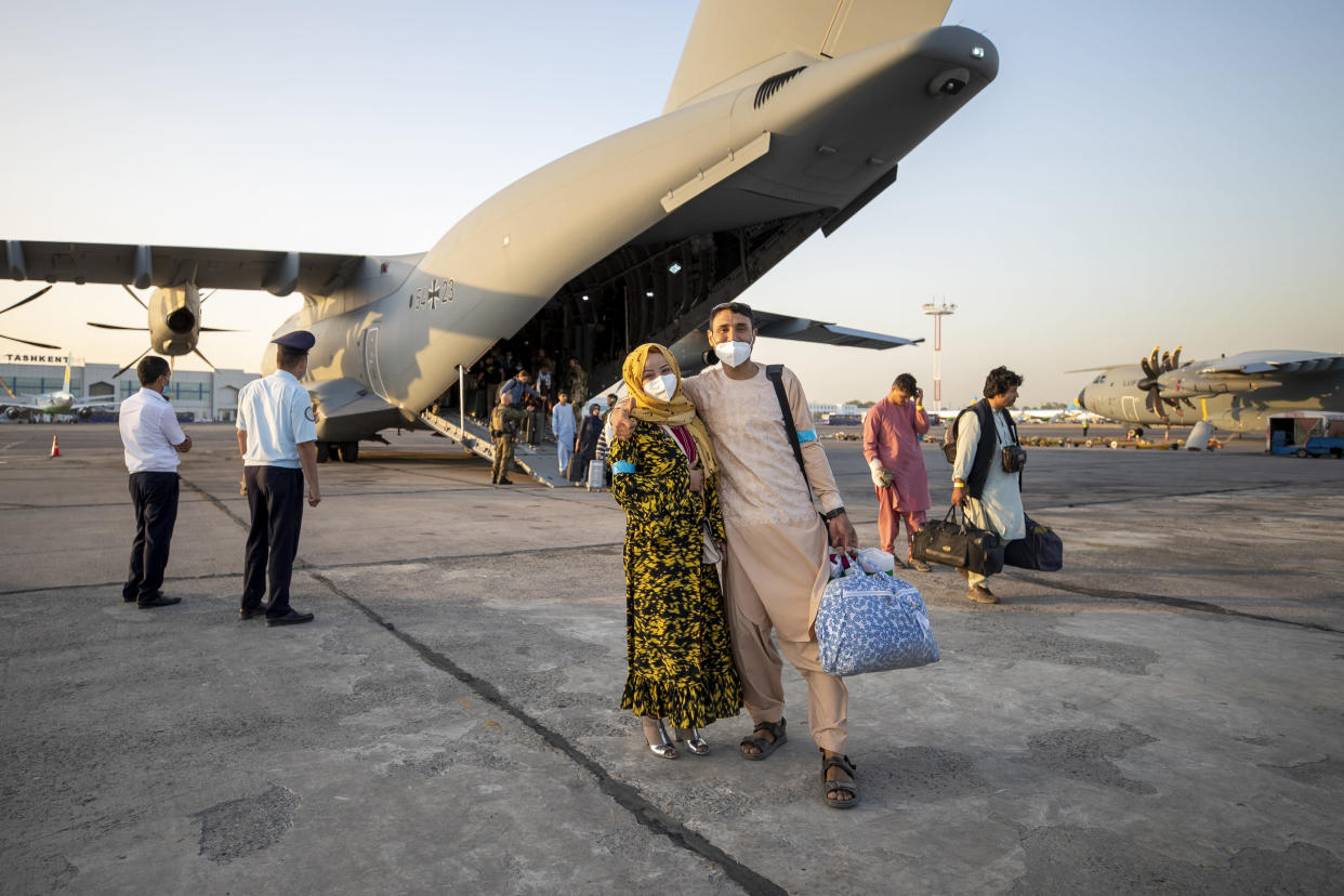 People evacuated from Afghanistan pose in front of a German Bundeswehr airplane after arriving at the airport in Tashkent, Uzbekistan, Tuesday, Aug. 17, 2021. (Bundeswehr via AP)