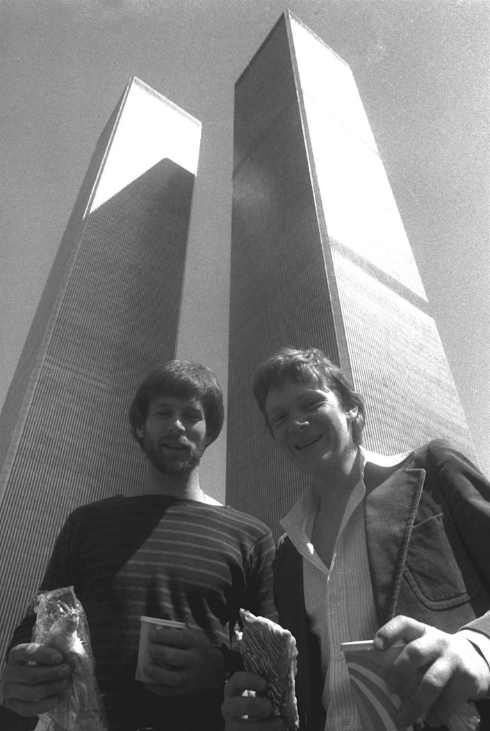 George Willig, left, and Philippe Petit prepare to catch a bite at the base of New York's twin World Trade Center Towers Wednesday, April 12, 1978. The two adventurers are more familiar with the skyscrapers from a different perspective; Petit for his tight rope walk between the two buildings, and Willig for his facade-climbing journey up the 110-story building in 1977. (AP Photo/Dave Pickoff)