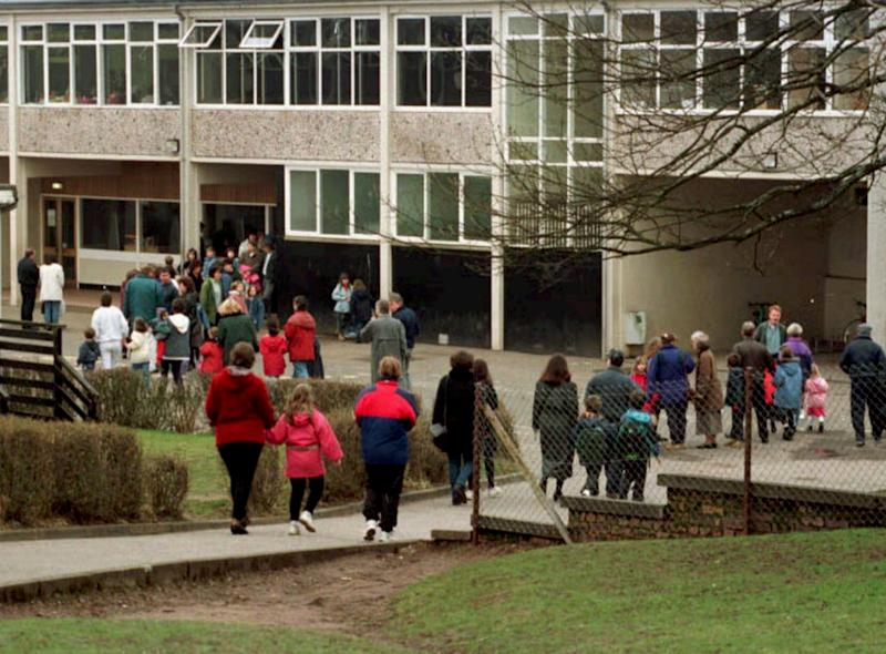FILE - In this March 22, 1996 file photo, children return to Dunblane Primary School, nine days after a gunman killed 16 children, their teacher and himself in Dunblane, Scotland. In March 1996, a 43-year-old man named Thomas Hamilton walked into a primary school in this central Scotland town of 8,000 people and shot to death 16 kindergarten-age children and their teacher with four legally held handguns. In the weeks that followed, people in the town formed the Snowdrop campaign - named for the first flower of spring - to press for a ban on handguns. Within weeks, it had collected 750,000 signatures. By the next year, the ban had become law. (AP Photo/Pool-File)