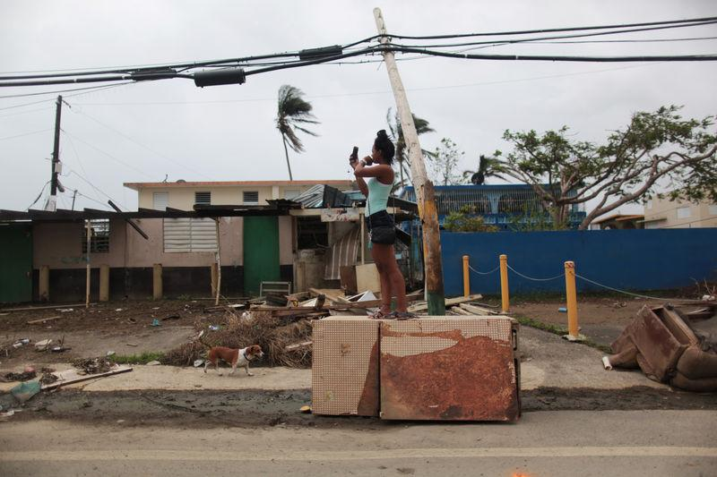 A woman stands on an overturned refrigerator while trying to get a mobile phone signal, after Hurricane Maria hit the island in September, in Toa Baja, Puerto Rico