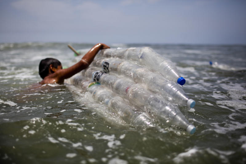 A boy gets into the sea with a surfboard made from plastic bottles as part of an environmental recyclying project, in Lima, on February 27, 2014 (AFP Photo/Ernesto Benavides)