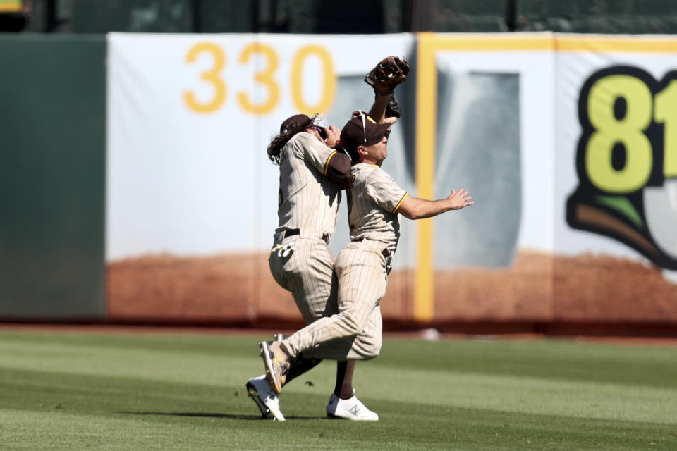 San Diego Padres' Adam Frazier, right, catches a fly ball next to teammate Jake Marisnick, left, on a ball hit by Oakland Athletics' Mark Canha during the ninth inning of a baseball game in Oakland, Calif., Wednesday, Aug. 4, 2021. (AP Photo/Jed Jacobsohn)
