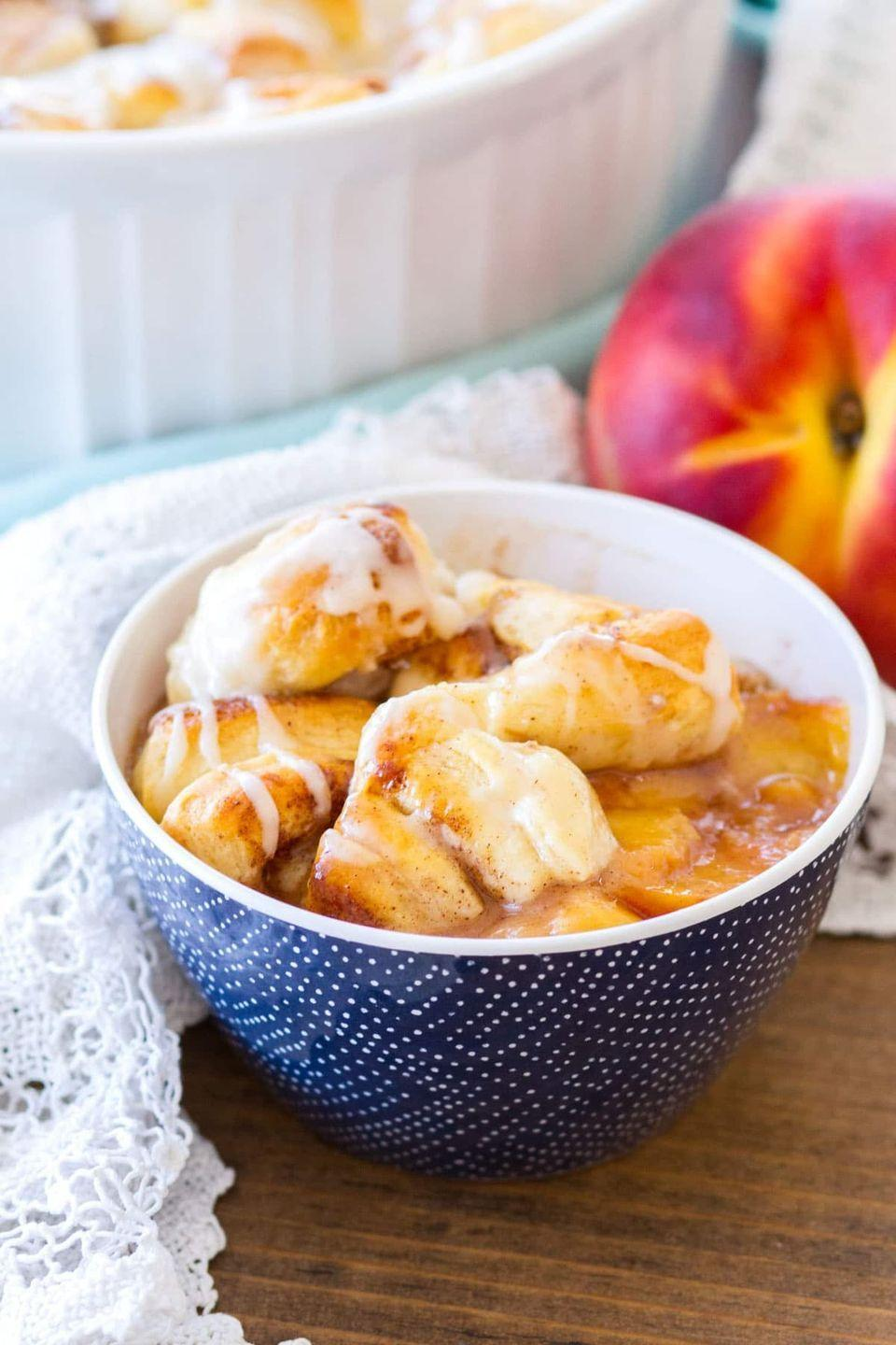 """<p>Looking to try a twist on your go-to peach cobbler? Give this version a go—it's like two delicious desserts in one.</p><p><strong>Get the recipe at <a href=""""https://www.julieseatsandtreats.com/easy-cinnamon-roll-peach-cobbler/"""" rel=""""nofollow noopener"""" target=""""_blank"""" data-ylk=""""slk:Julie's Eats and Treats"""" class=""""link rapid-noclick-resp"""">Julie's Eats and Treats</a>.</strong></p><p><a class=""""link rapid-noclick-resp"""" href=""""https://go.redirectingat.com?id=74968X1596630&url=https%3A%2F%2Fwww.walmart.com%2Fsearch%2F%3Fquery%3Dpioneer%2Bwoman%2Bcooking%2Btools&sref=https%3A%2F%2Fwww.thepioneerwoman.com%2Ffood-cooking%2Frecipes%2Fg36382592%2Fpeach-desserts%2F"""" rel=""""nofollow noopener"""" target=""""_blank"""" data-ylk=""""slk:SHOP COOKING TOOLS"""">SHOP COOKING TOOLS</a></p>"""