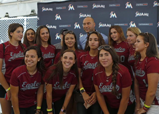 Miami Marlins CEO Derek Jeter poses for photos with the Marjory Stoneman Douglas softball team before the Marlins' spring training baseball game against the St. Louis Cardinals on Friday, Feb. 23, 2018, in Jupiter, Fla. The Marlins honorin Stoneman Douglas shooting victims with special hats, T-shirts, patches. MLB teams wore hats to honor Marjory Stoneman Douglas High School in Parkland, Fla., where 17 people were fatally shot nine days ago. Stoneman Douglas baseball coach Todd Fitz-Gerald and his two sons were guests of the Houston Astros for their spring opener against the Washington Nationals. Members of the school's baseball and softball teams were guests of the Marlins and mingled on the field with players, coaches and Jeter. (David Santiago/Miami Herald via AP)