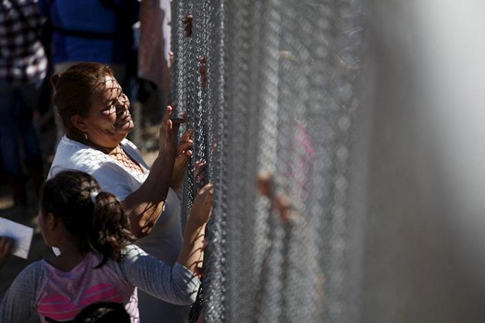 FILE PHOTO: A woman touches a family member through the border fence between Ciudad Juarez and El Paso, United States, after a bi-national Mass in support of migrants in Ciudad Juarez, Mexico, February 15, 2016. REUTERS/Jose Luis Gonzalez
