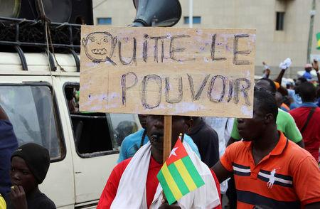 """A man holds up a sign which reads, """"leave the power"""", during opposiition protest to call for the immediate resignation of President Faure Gnassingbe in Lome, Togo, September 7, 2017. REUTERS/Noel Kokou Tadegnon"""