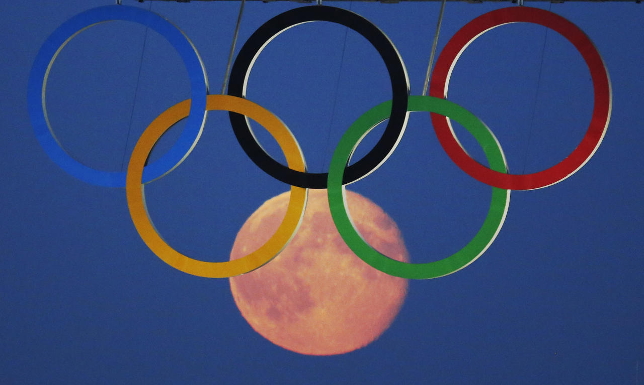 The full moon rises through the Olympic Rings hanging beneath Tower Bridge during the London 2012 Olympic Games August 3, 2012.  REUTERS/Luke MacGregor  (BRITAIN - Tags: SPORT OLYMPICS CITYSPACE TPX IMAGES OF THE DAY ENVIRONMENT)