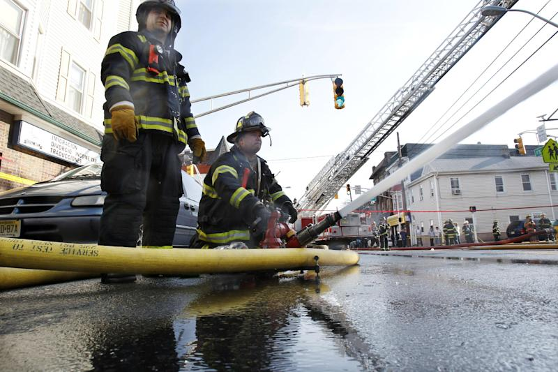 Harrisson firefighters Frank Cupo, left, and Jim Patterson spray water as they battle a multialarm fire at a building in Harrison, N.J., Sunday, March 10, 2013. The blaze gutted a two-story building with a restaurant on the ground floor and then spread to a two-story residential building. There are reports of at least four firefighters sustaining minor injuries. (AP Photo/Mel Evans)