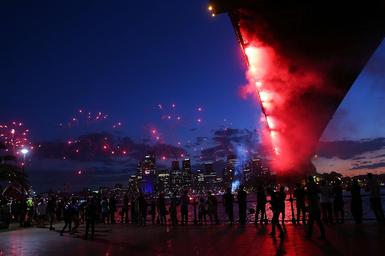 SYDNEY, AUSTRALIA - DECEMBER 31:  People watch fireworks under The Sydney Harbour Bridge during New Years Eve celebrations on Sydney Harbour on December 31, 2012 in Sydney, Australia.  (Photo by Brendon Thorne/Getty Images)