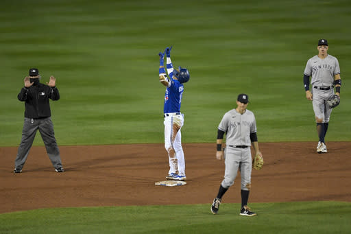 Toronto Blue Jays' Lourdes Gurriel Jr., second from left, celebrates after advancing to second on a single as New York Yankees second baseman DJ LeMahieu, second from right, and right fielder Aaron Judge, right, look on during the sixth inning of a baseball game in Buffalo, N.Y., Wednesday, Sept. 23, 2020. Teoscar Hernndez and Randal Grichuk scored. (AP Photo/Adrian Kraus)