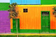 <p>A home exterior in Peru packs a punch with saturated shades of green, orange, and purple.</p>