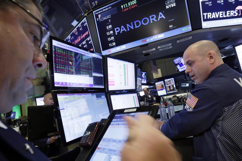 FILE - In this Oct. 23, 2015 file photo, Specialist Mark Fitzgerald, right, works at the post on the floor of the New York Stock Exchange that trades Pandora.  Pandora says it has revamped its $5 a month Internet radio service, Thursday, Sept. 15, 2016,  giving listeners the ability to skip and replay more songs. (AP Photo/Richard Drew)