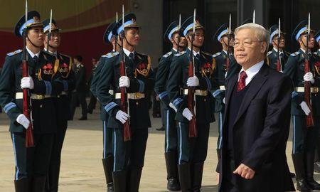 Vietnam's Communist Party's General Secretary Nguyen Phu Trong walks past the guard of honour during celebrations to commemorate the 70th anniversary of the establishment of the Vietnam People's Army in Hanoi